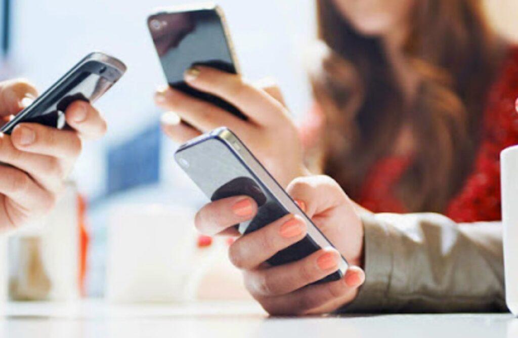 Pessoas com celular na mão, acessando aplicativos de Delivery.