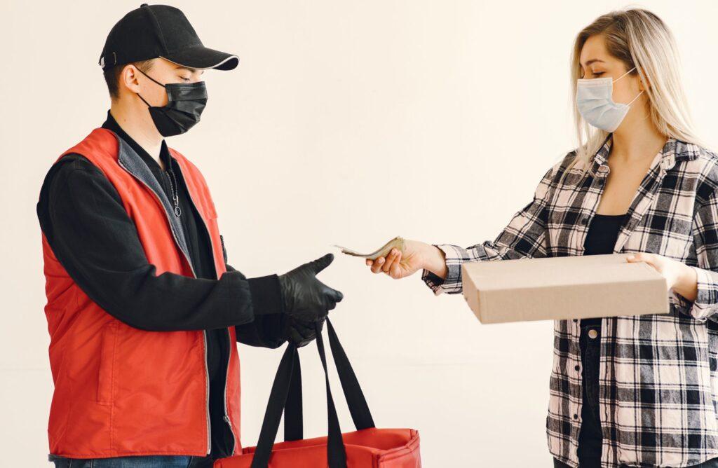 duas pessoas, um entregador, motoboy, uma moça recebendo a encomenda